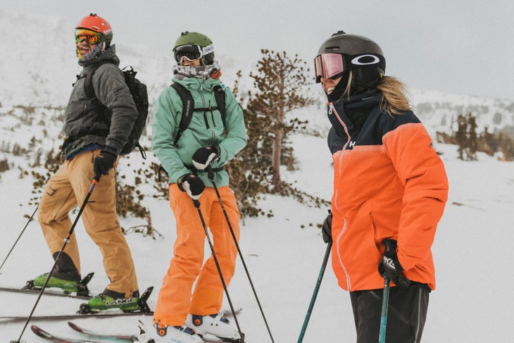 Three people stand on skis at Mammoth Mountain and laugh. All wearing different combinations of black, orange, and light teal. Rolling hills covered…