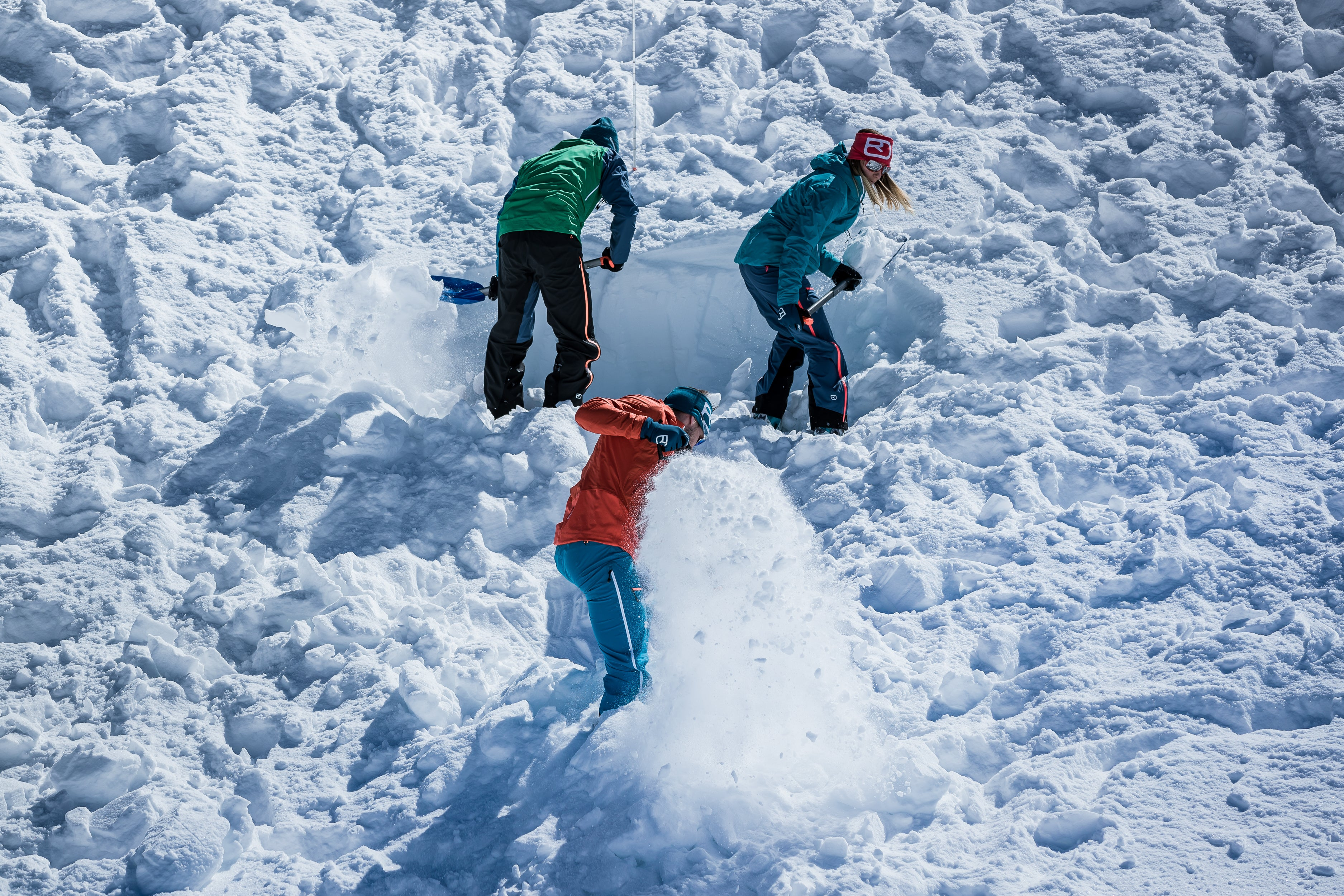 Backcountry skiers dig in snow to recover buried avalanche transceiver